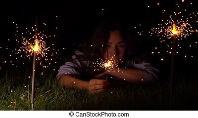 Pensive young woman on the grass with burning sparkler at night. Super slow motion video shot at 500 fps