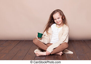 little girl sitting on the floor and drinking tea - a little...
