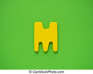 Capital letter M Yellow letter M from wood on green...