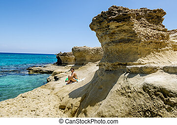 Girl resting on the beach among the rocks in Protaras...