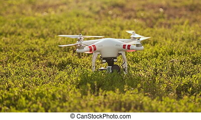 Drone take off on a grassy field at sunset
