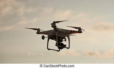 Quadcopter With Camera Flying On Sunset.