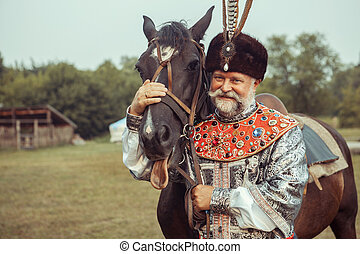 King dressed in medieval costume is stroking his horse on...