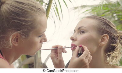 Closeup of model receiving makeup during photo shoot, makeup...