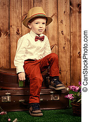 vintage travel - Cute little boy in elegant clothes sitting...