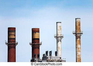 Smoke Stacks - Four smoke stacks atop factories or...