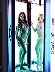 Beautiful ladies posing in vertical tanning booth - Image of...