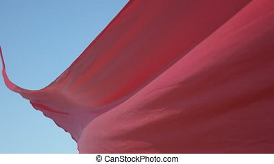 Flowing red fabric - Against backdrop of blue sky flying red...