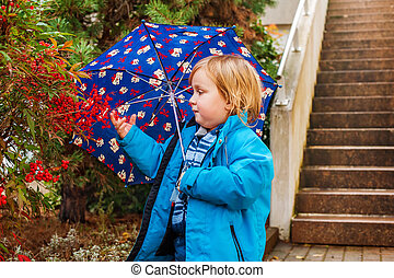 Cute toddler boy with umbrella playing outdoors on a rainy...