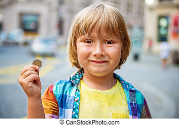 Outdoor portrait of a cute little boy in a city, holding 2 euro coin