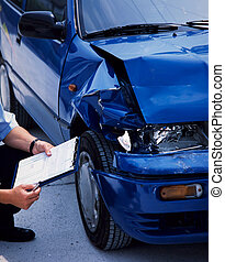 damaged car - surveyor at a blue damaged car after an...
