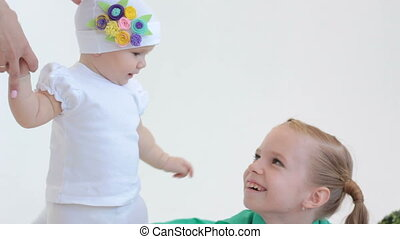 Baby girl stroking her sister - close-up of cute baby in...