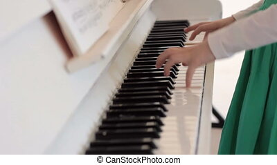 Girls hands playing piano with notes - Close-up of...