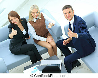 Businesspeople With Laptop Having Meeting In Office Showing...