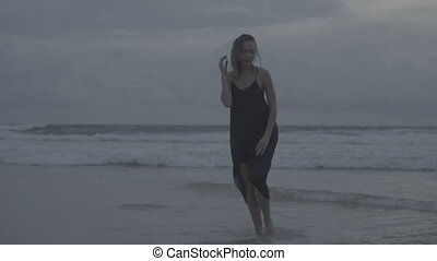 Sensual glamour woman in black dress and wet hair on a beach...