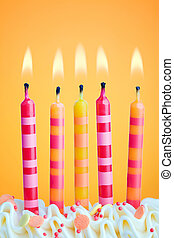 Birthday candles - Five birthday candles against an orange...