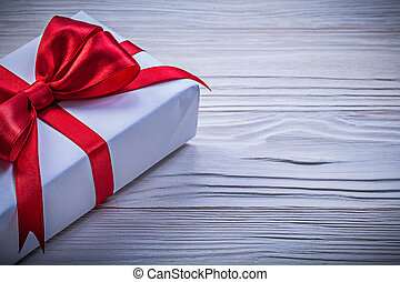 Gift box with red ribbon directly above holidays concept