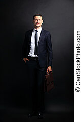 Portrait of a business man with briefcase isolated on black...