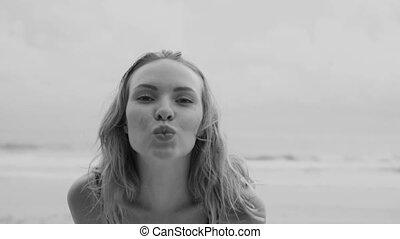 Sensual glamour woman in black bikini with hand fan on a beach
