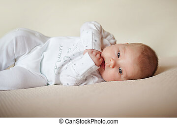 child is lying on bright plaid in white pajamas