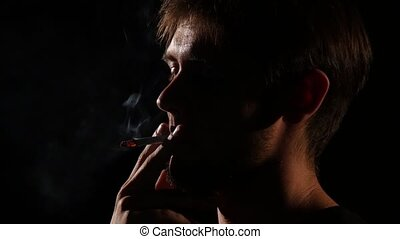 Man beard lighting a cigarette. Backlight. Close up - Young...