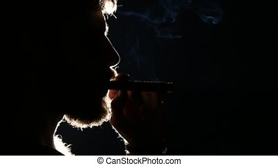 Man smokes cigar. Black. Silhouette. Close up - Man smokes...