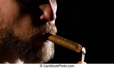 Man in a dark room, smoking a cigar. Close up - Man in a...