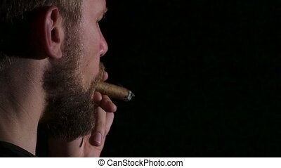 Video as a man smokes a big cigar. Black. Close up - Detail...