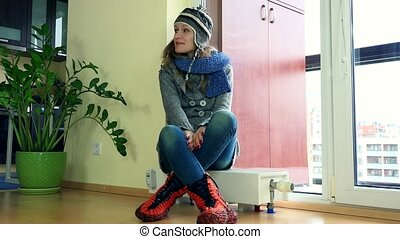Cheerful girl strip warm clothes sitting on heater near...