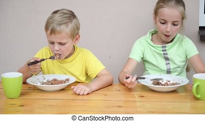 two cute kid eating at table