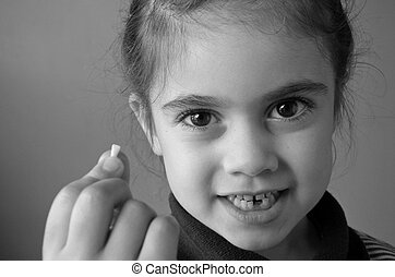 Proud young girl holds her first falling milk teeth - Proud...