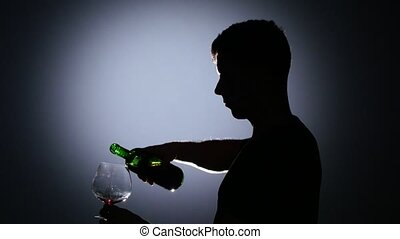 Man pouring red wine into a glass. Back light - Man pouring...