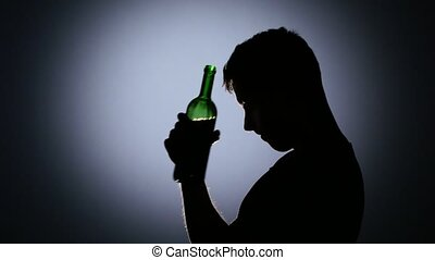 Man depressed and drinking wine. Back light. Close up -...