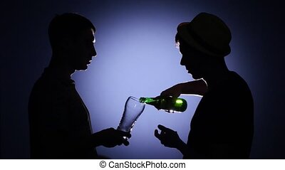 Two male friends talking and drinking beer. Back light - Two...