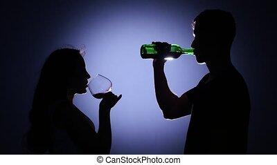 Couples dancing and drinking at evening party. Back light -...