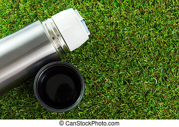 Metallic thermos flask - Close up of thermos flask on green...