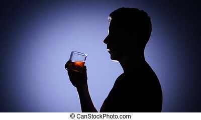 Young man drinking whiskey. Alcoholic subjects. Back light -...