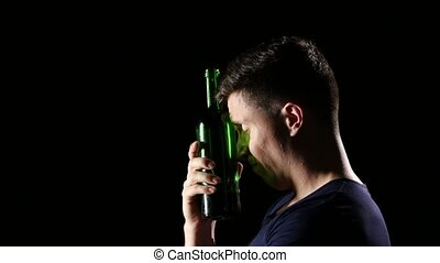 Sad young man drinking wine with a throat. Black. Close up -...
