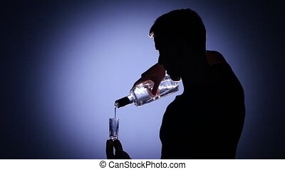 Man pouring vodka into a glass and drink it. Back light -...