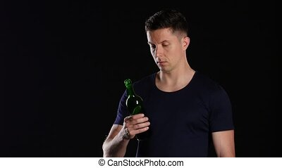 Alcohol addiction. Man drinking from a bottle of red wine....