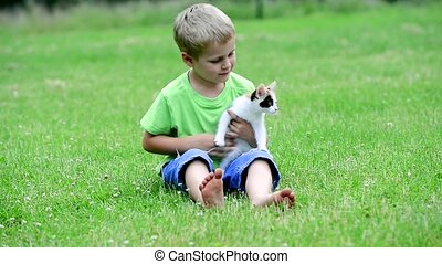 boy playing with kitten outdoor