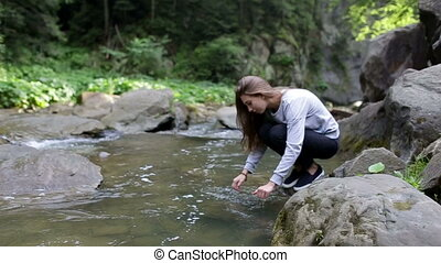 Young woman washing her hands in mountain river