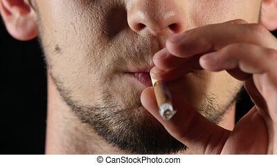 Young guy smokes a brown cirarette. Black. Close up - Bad...