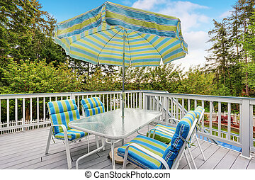 View of patio table set with umbrella in green and blue colors.