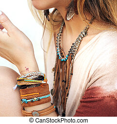 Female neck and hands with many boho bracelets, leather...