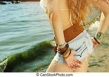 Woman buttock dirty with sand against sunny seascape, boho...