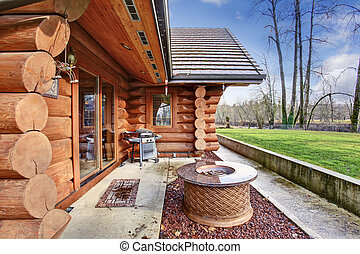 Large log cabin house exterior with patio area.