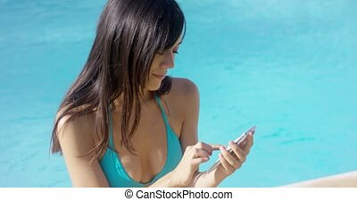 Attractive young woman sending a text message