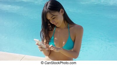 Pretty young woman checking her mobile poolside - Pretty...