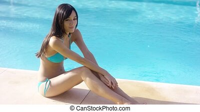 Exotic brunette wearing blue bikini sits by pool...